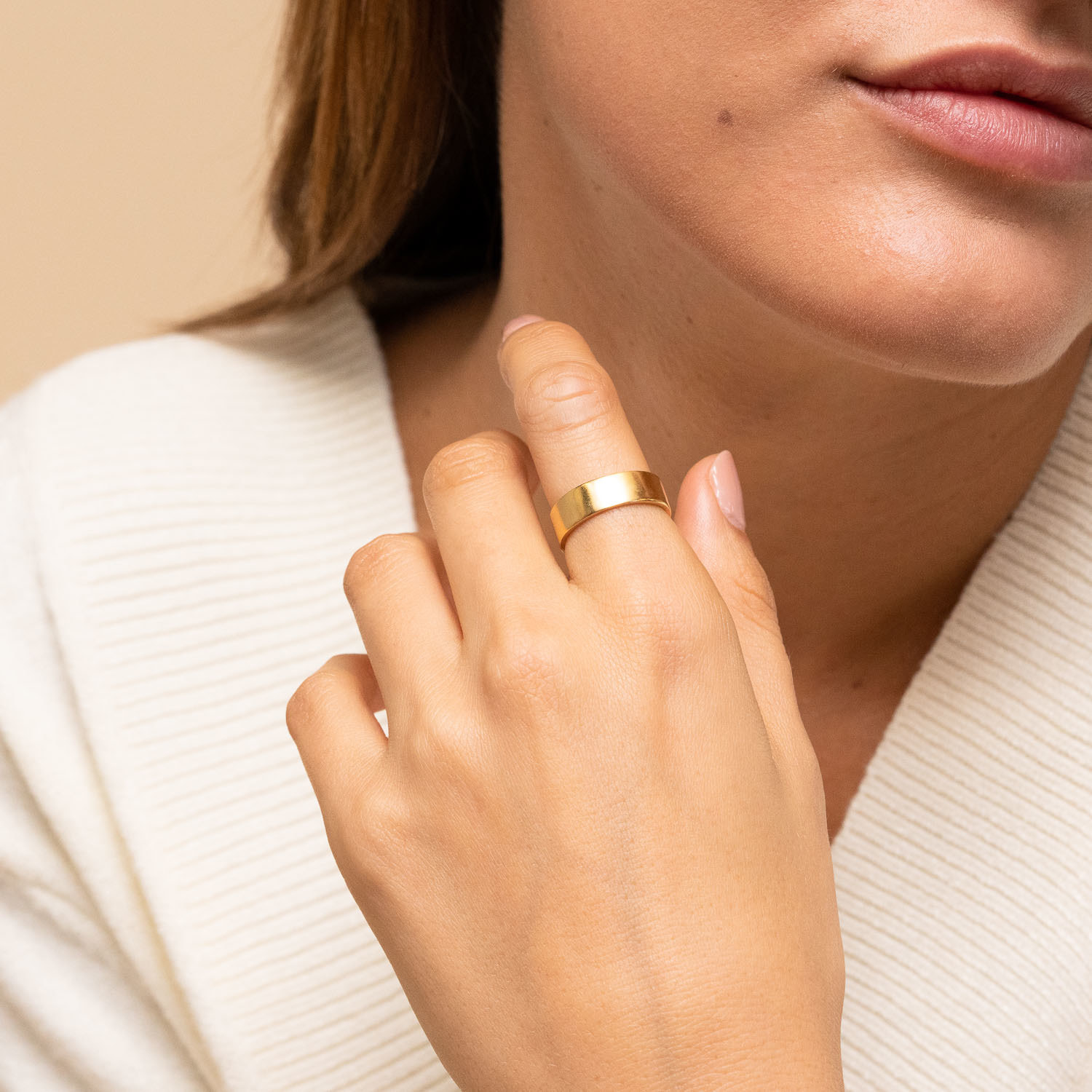Model wearing gold ring on index finger