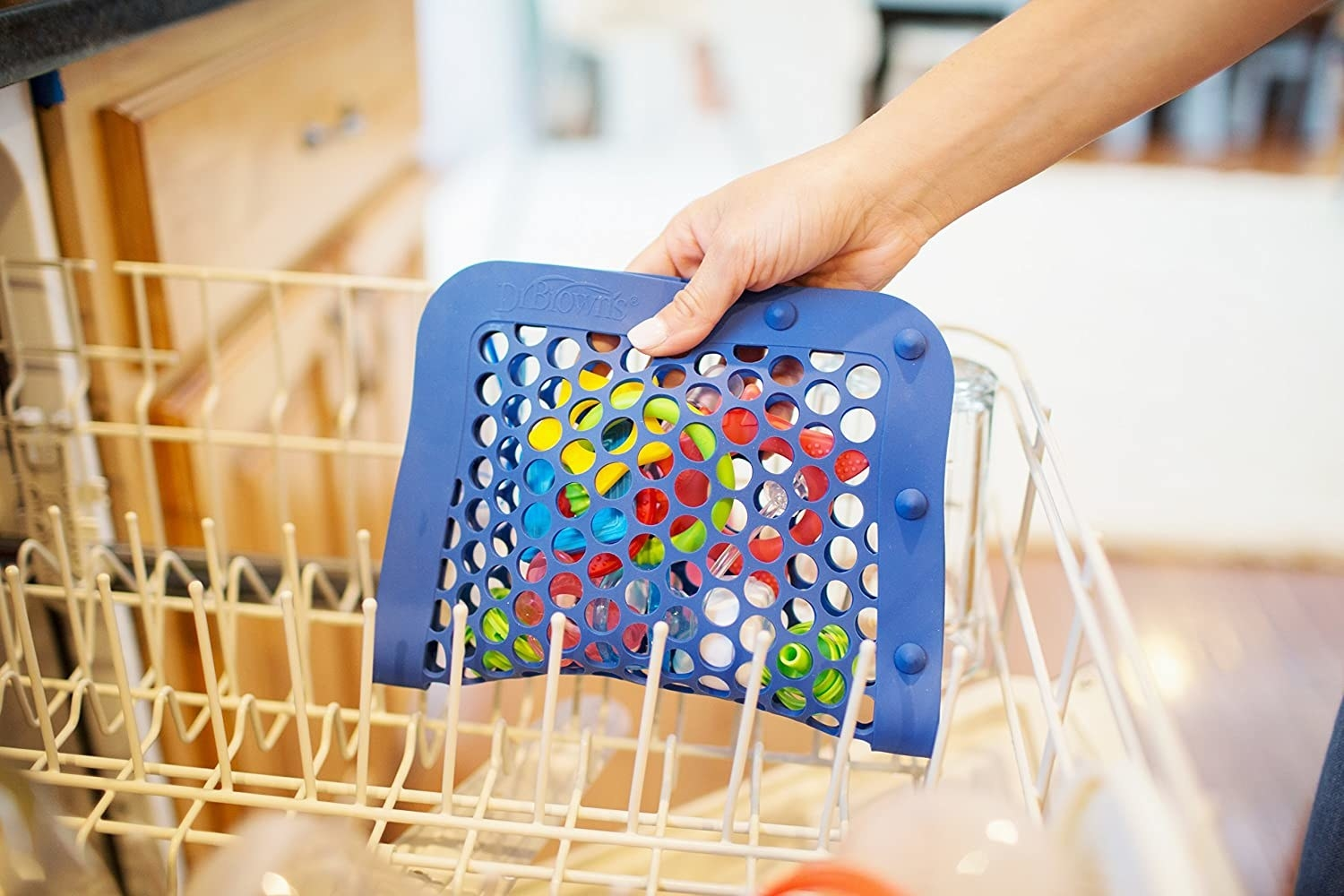 A person placing the filled pouch onto the top rack of their dishwasher