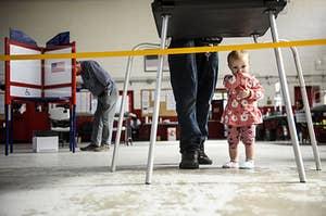 婴儿站在她父亲的双脚在选举日投票站。