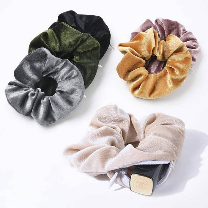 Six velvet scrunchies, one with a lipstick coming out of the pocket