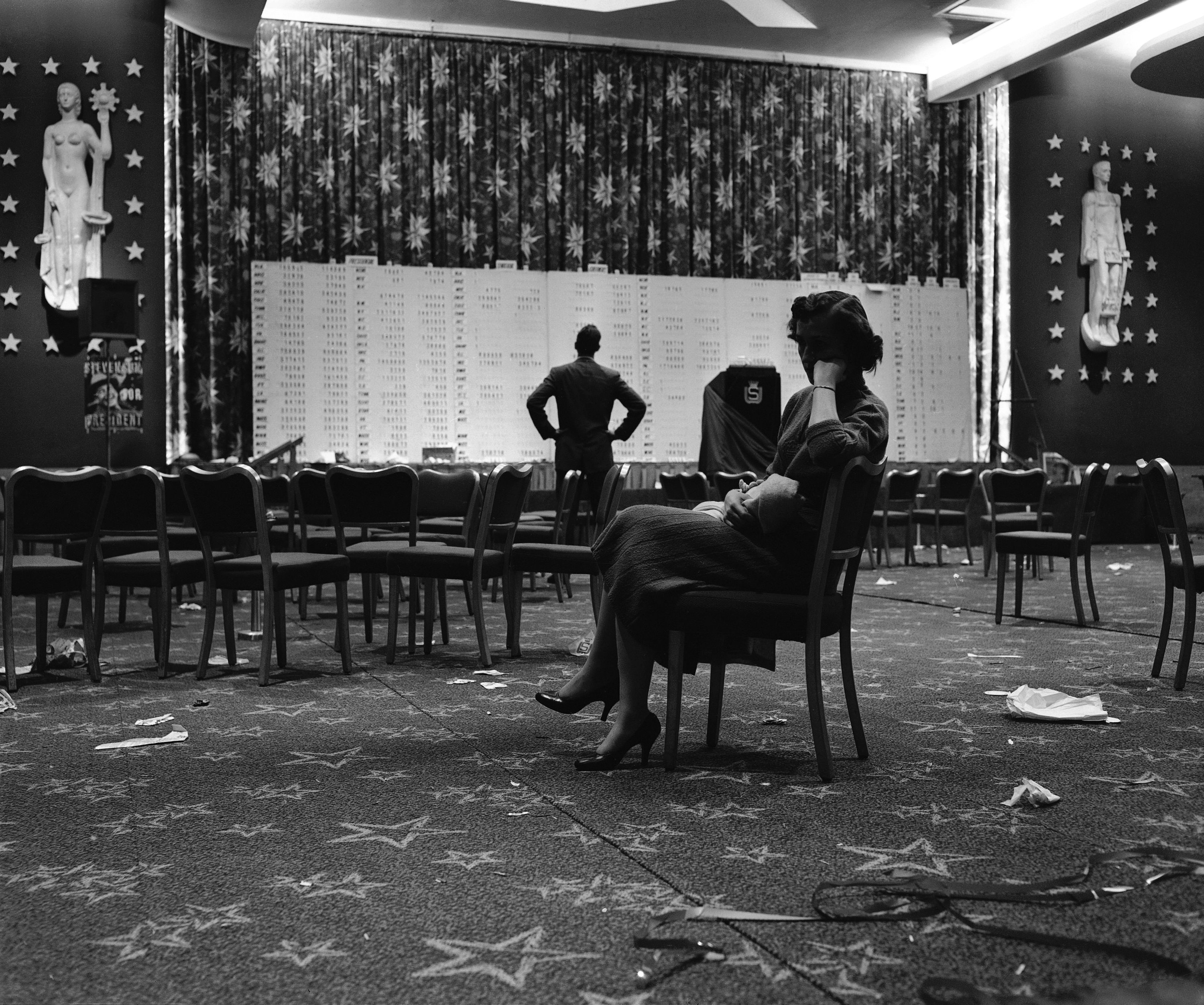 A woman in a chair looking sad in an empty hall.