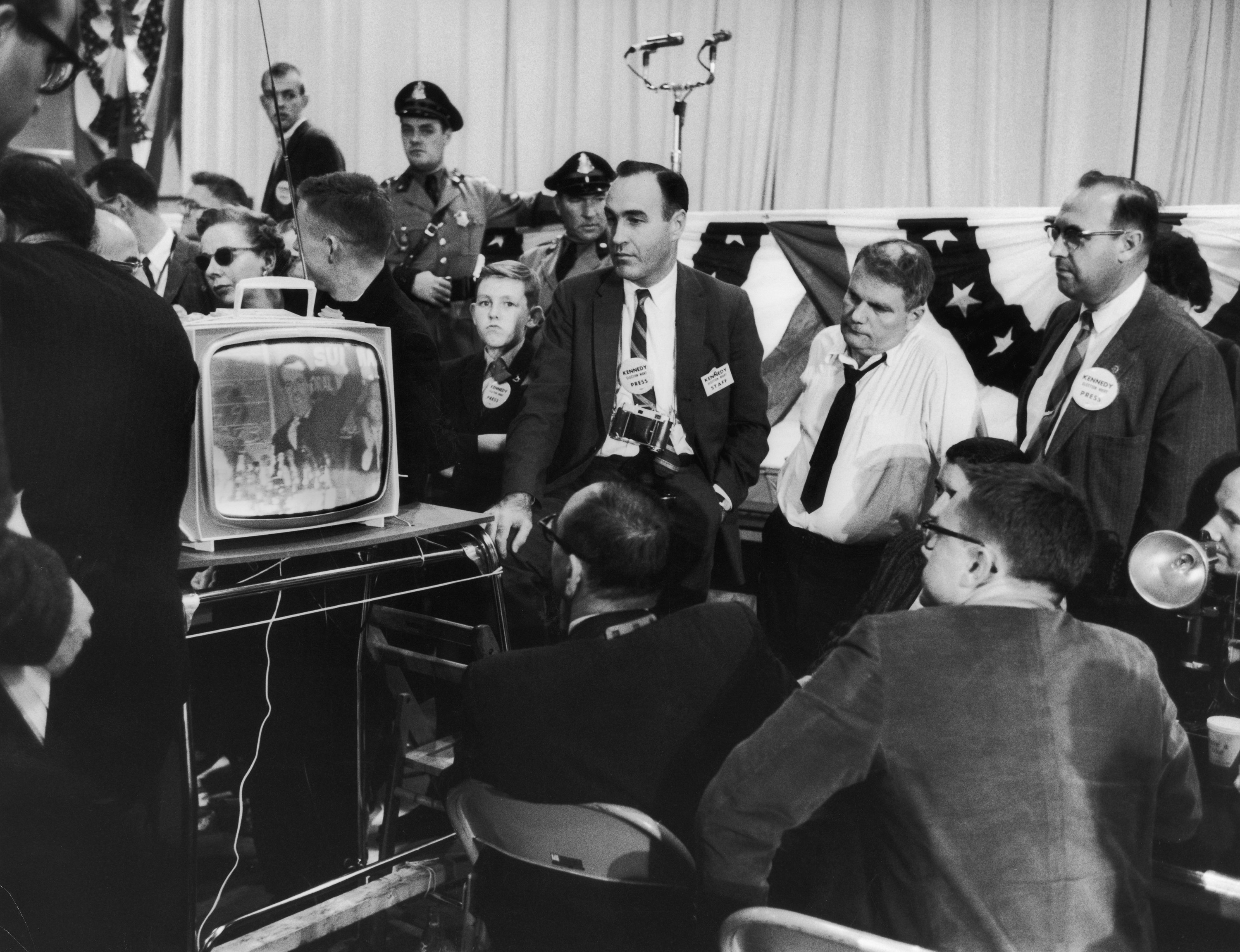 Men in black-and-white photo crowded around a TV
