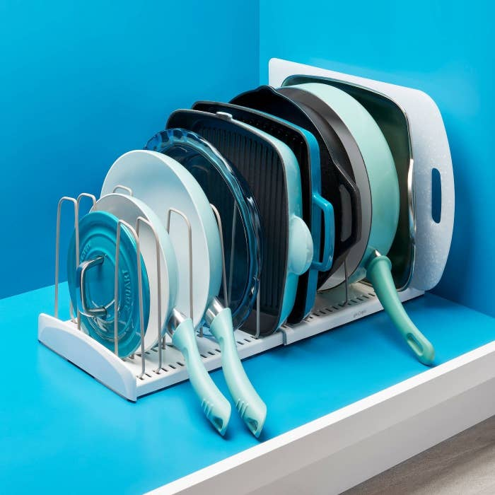White cookware rack with gray dividers holding blue and green pans