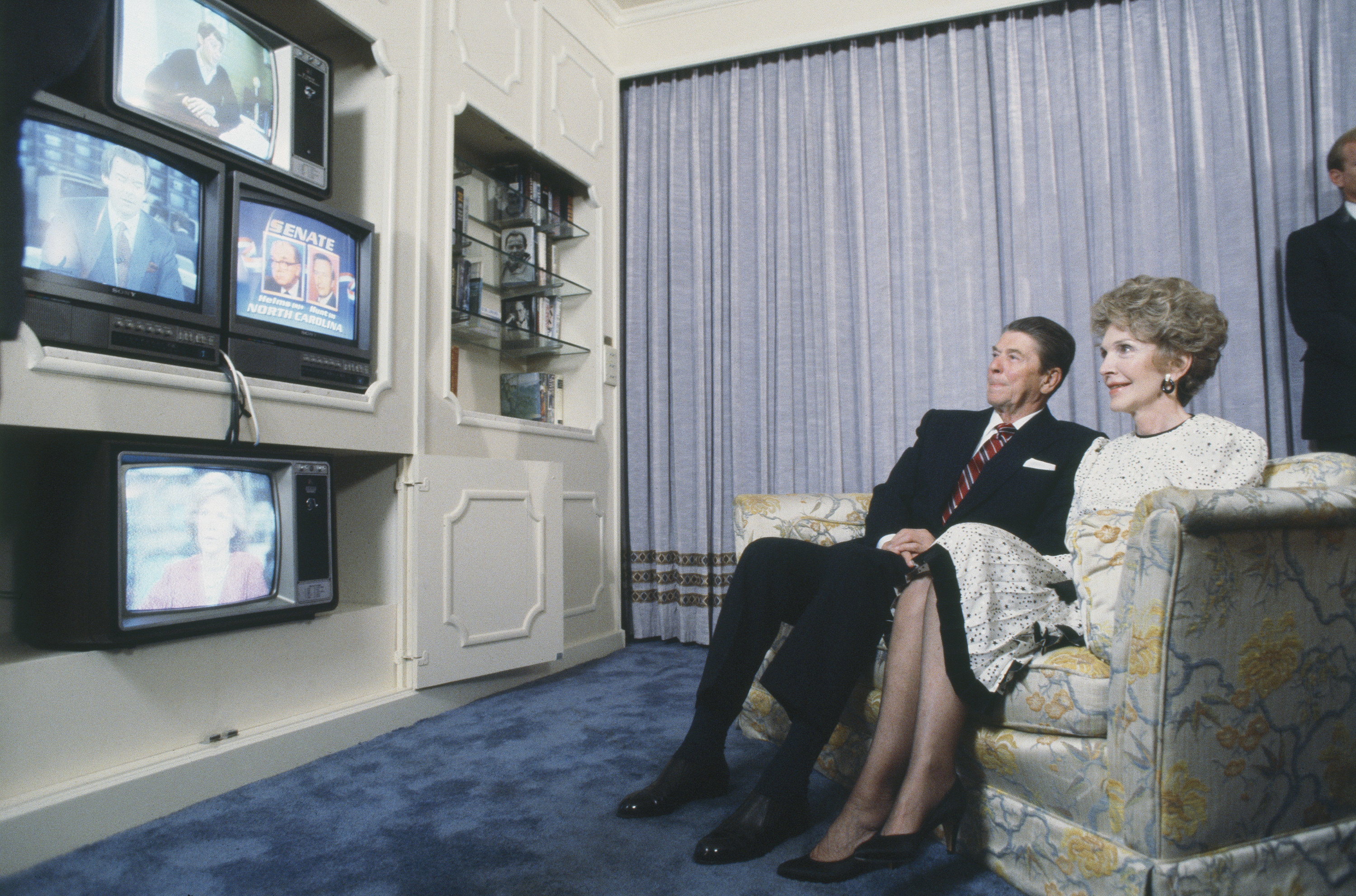 Ronald and Nancy Reagan watching multiple televisions