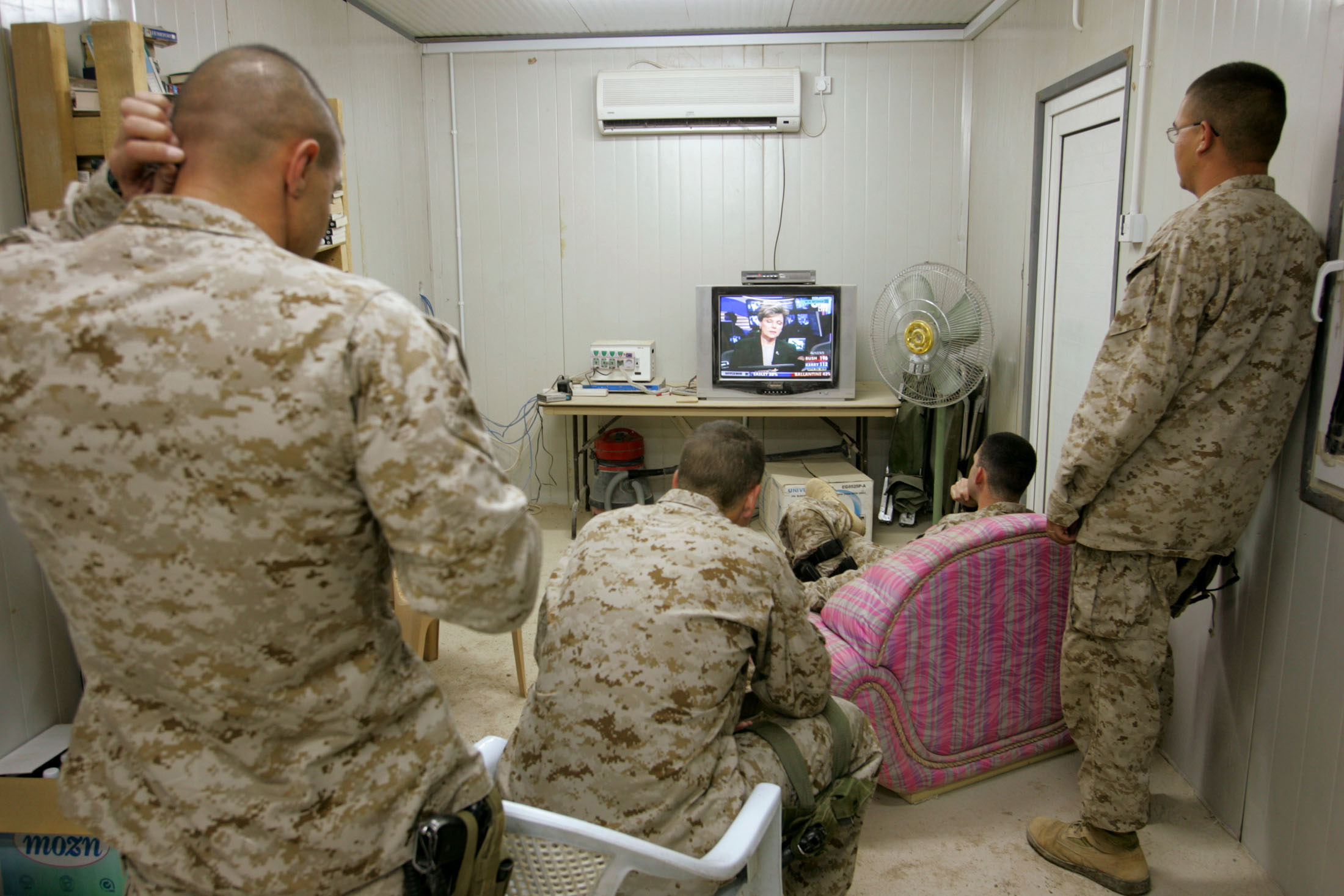 Men in camouflage watching a television with election results