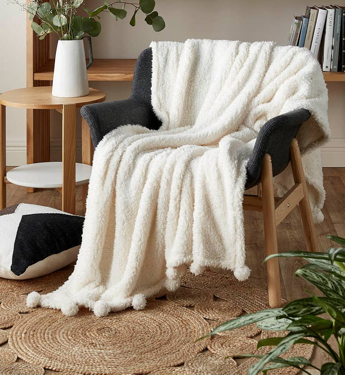 A soft sherpa blanket with pom poms on the trim draped over a chair