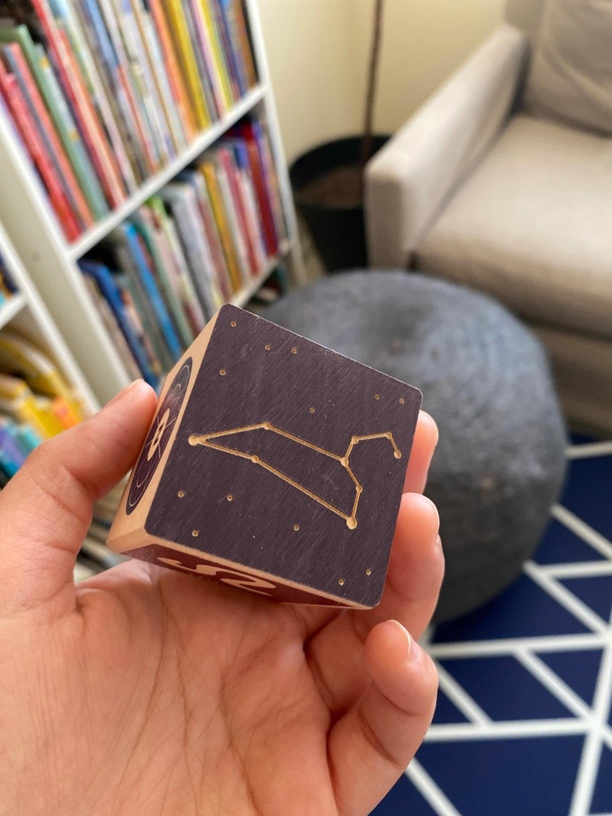 Reviewer's hand holding one of the blocks featuring a constellation