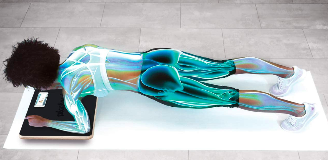 Model in plank position while placing wrists and elbows on a gold interactive Plankboard