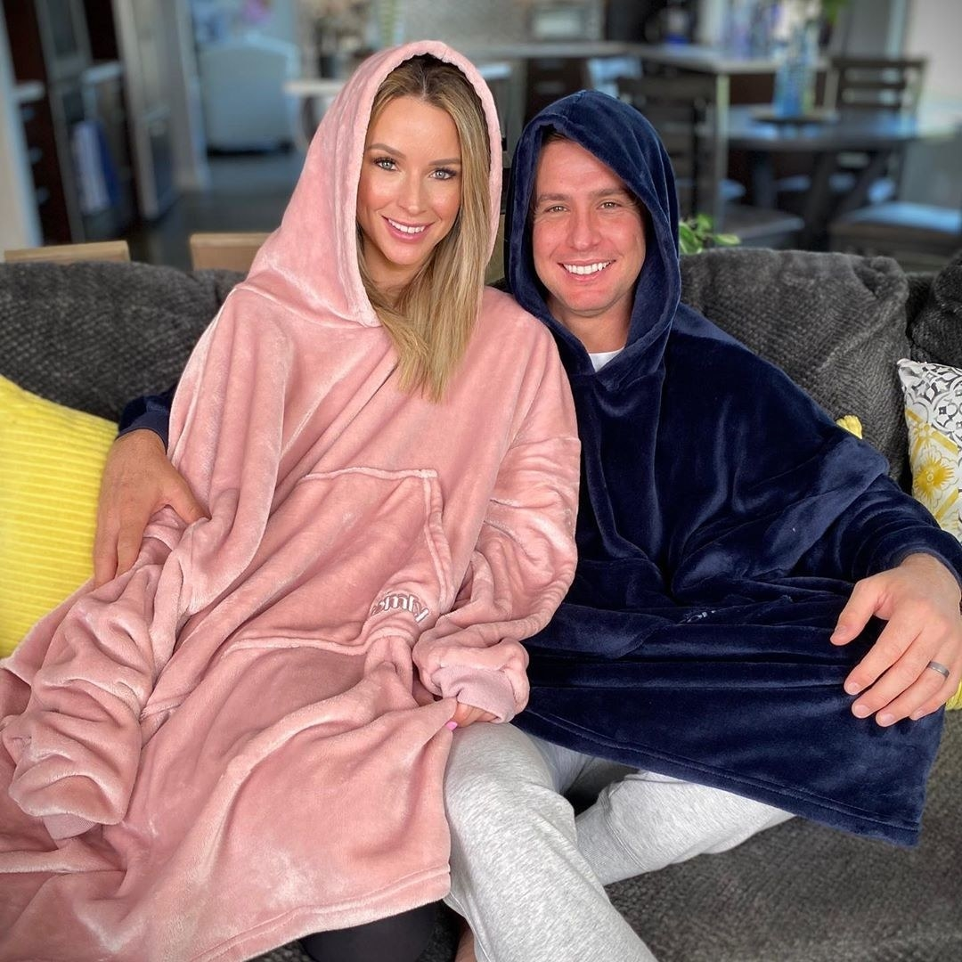Two people sitting on a couch wearing oversized hoodies