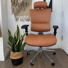 Leather office chair on wheels with padded seat, headrest, arm rests, and rounded lumbar support