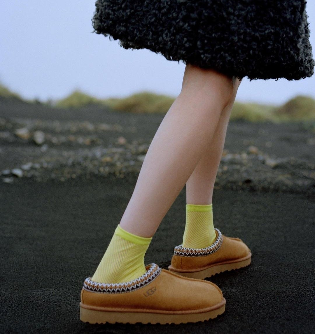 A person wearing Ugg slippers with socks