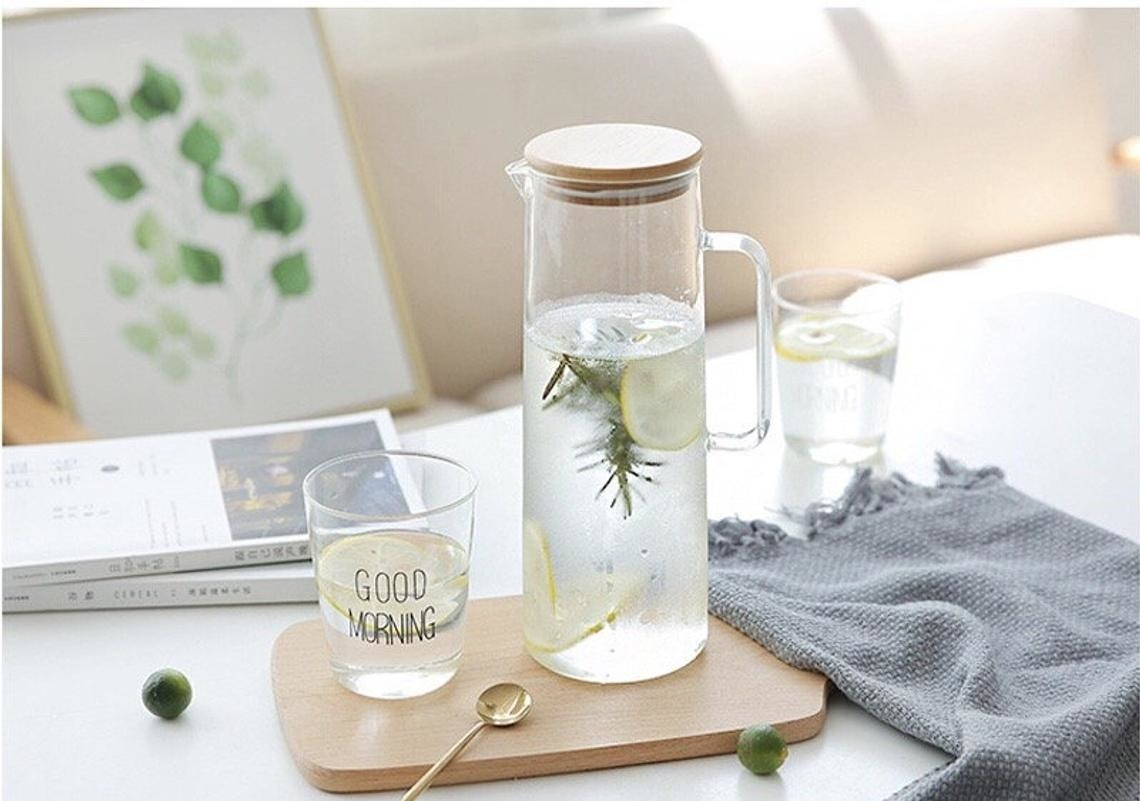 glass water kettle jar with wood lid resting on a coffee table
