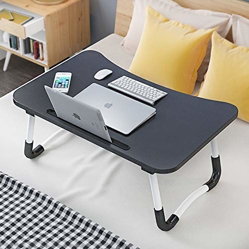 The table placed on a bed. A laptop, tablet, keyboard, mouse, and a phone are kept on the table.