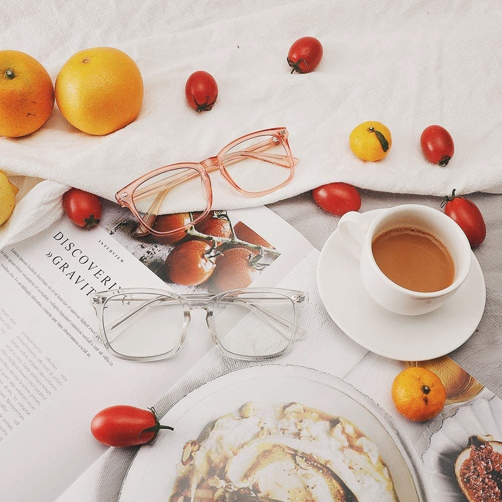 Two pairs of glasses on a table next to fruits and a cup of coffee