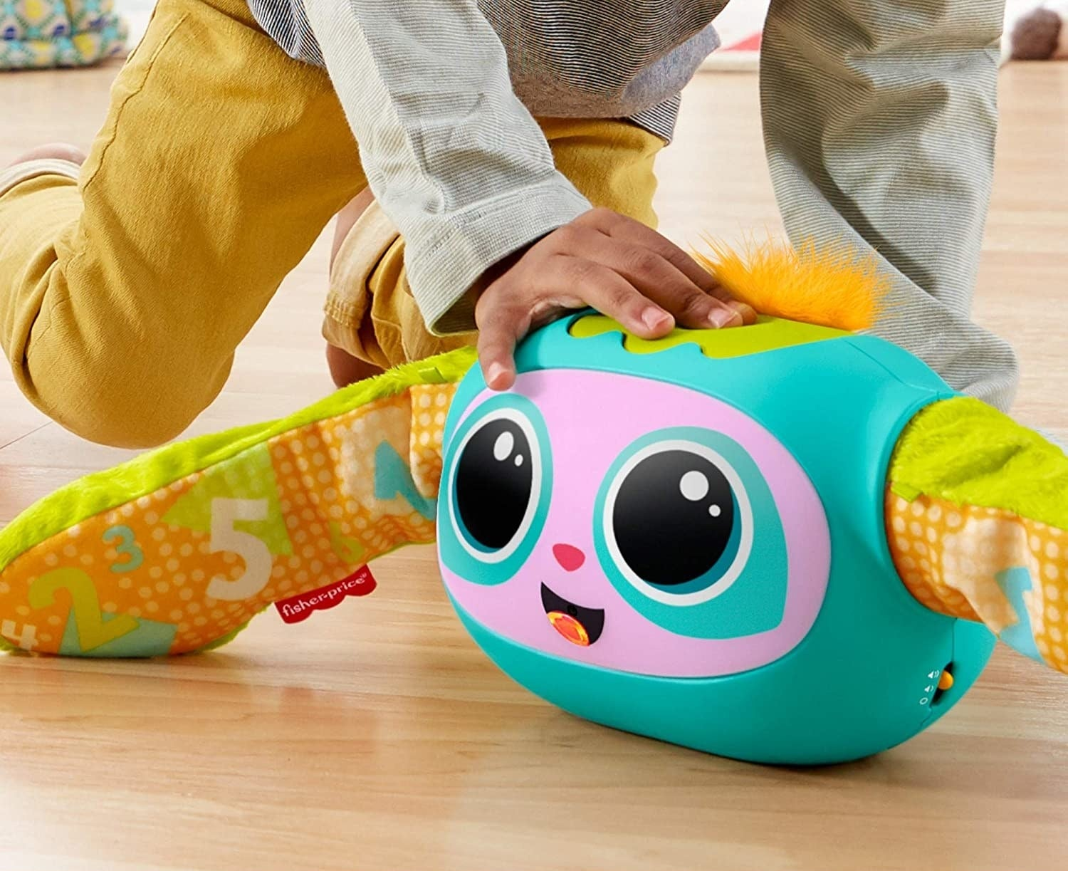 Child model's hand playing with Rovee toy on floor
