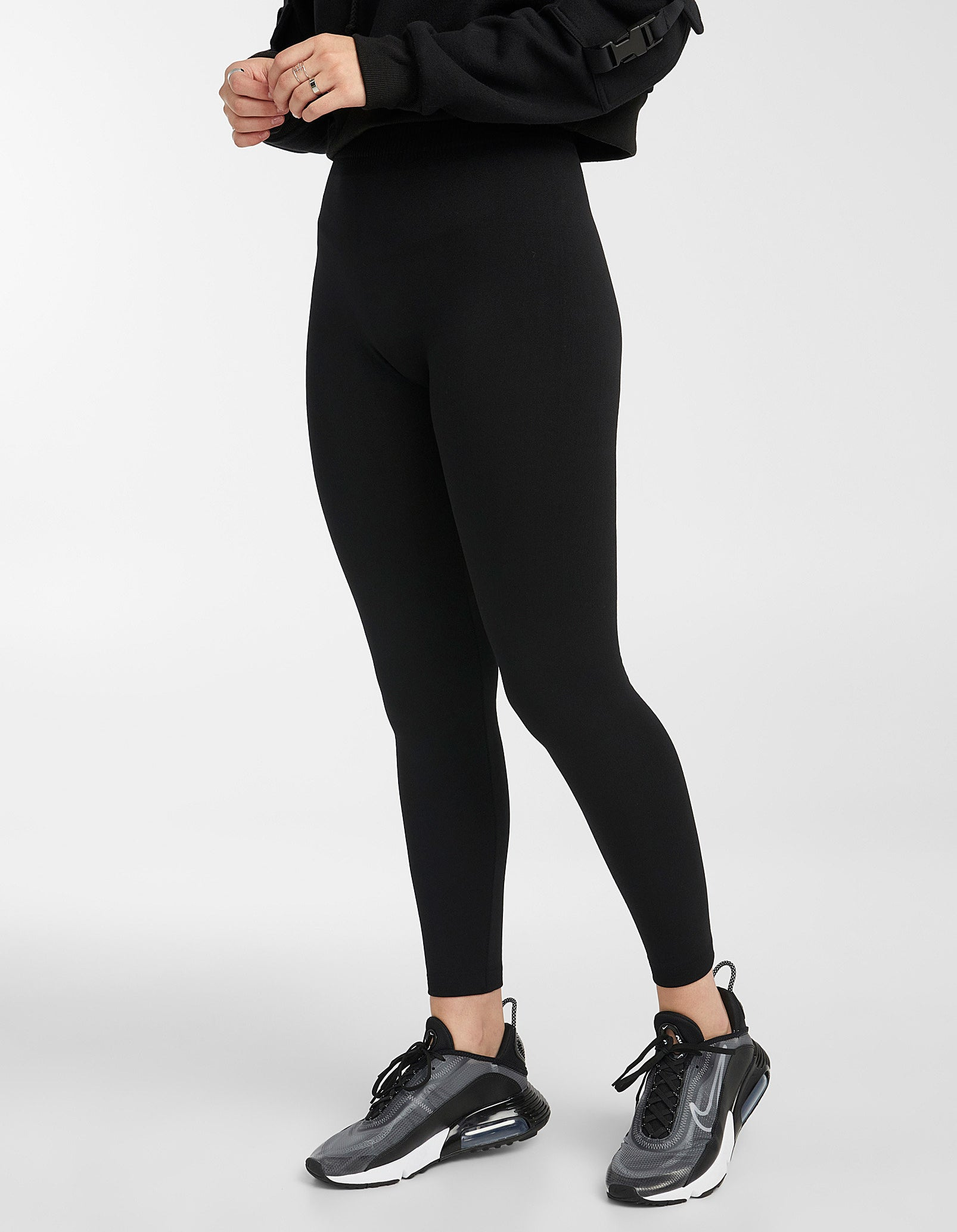 A person wearing leggings and running shoes