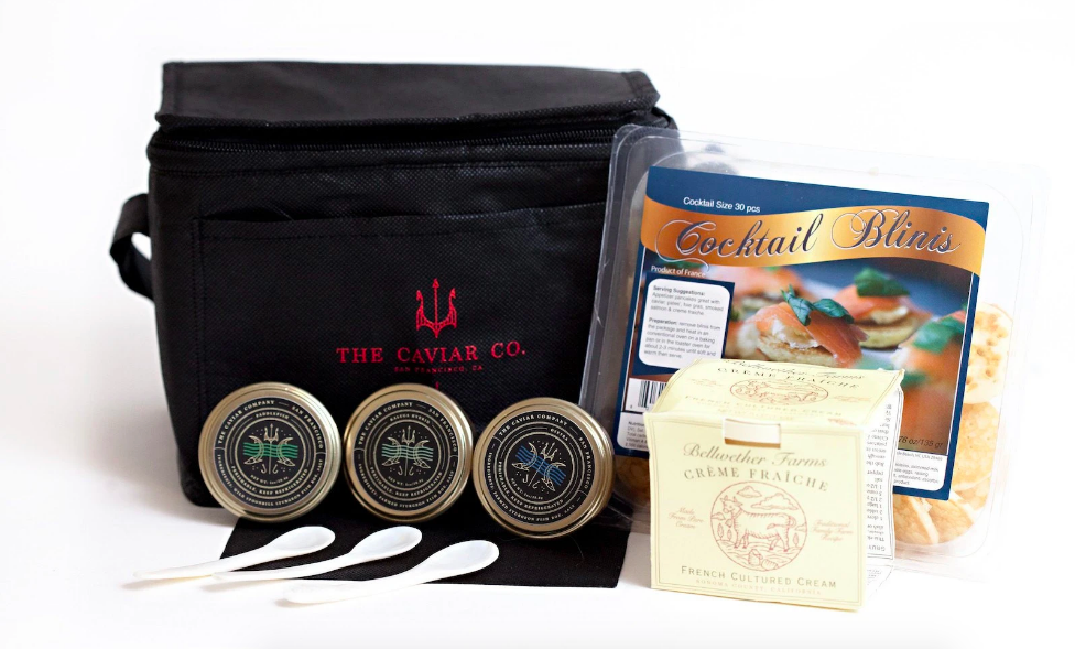 Full caviar kit with three jars, packet of blinis, creme, and carrier bag