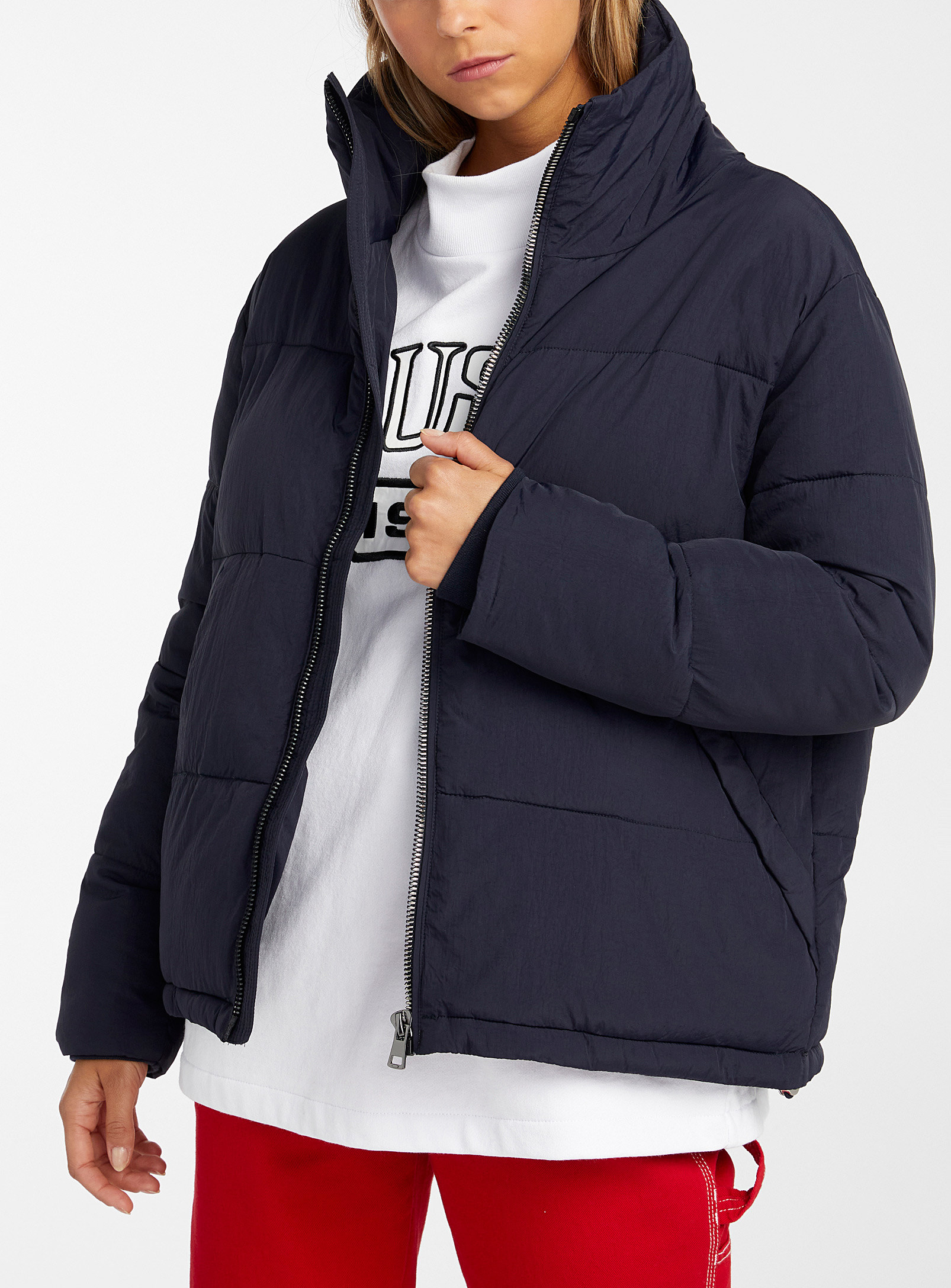 A person wearing a soft puffer jacket over a shirt