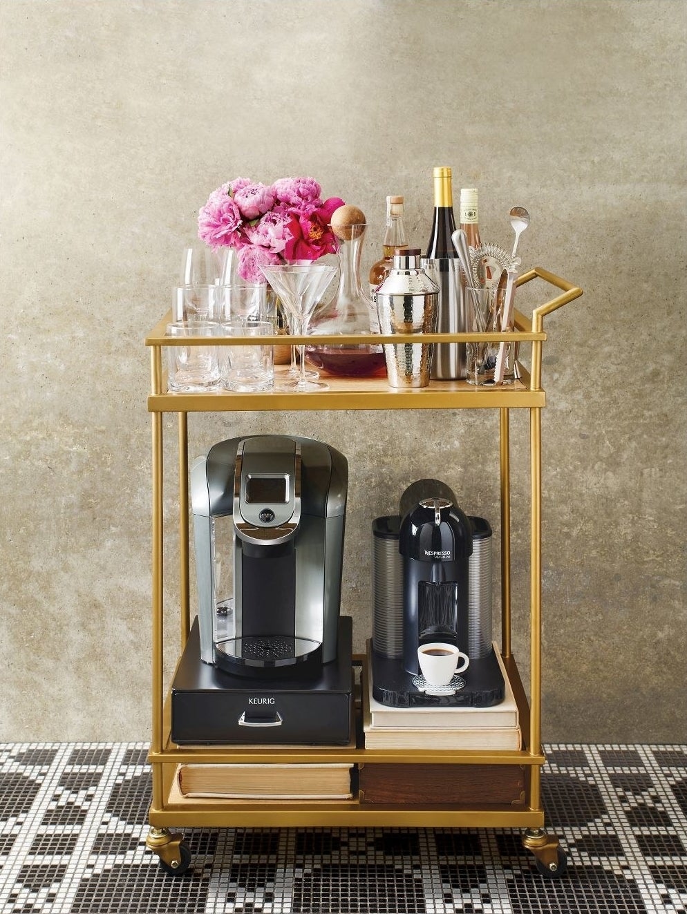 Wood and gold bar cart with black wheels carrying coffee machines on the bottom and cocktail shakers on top