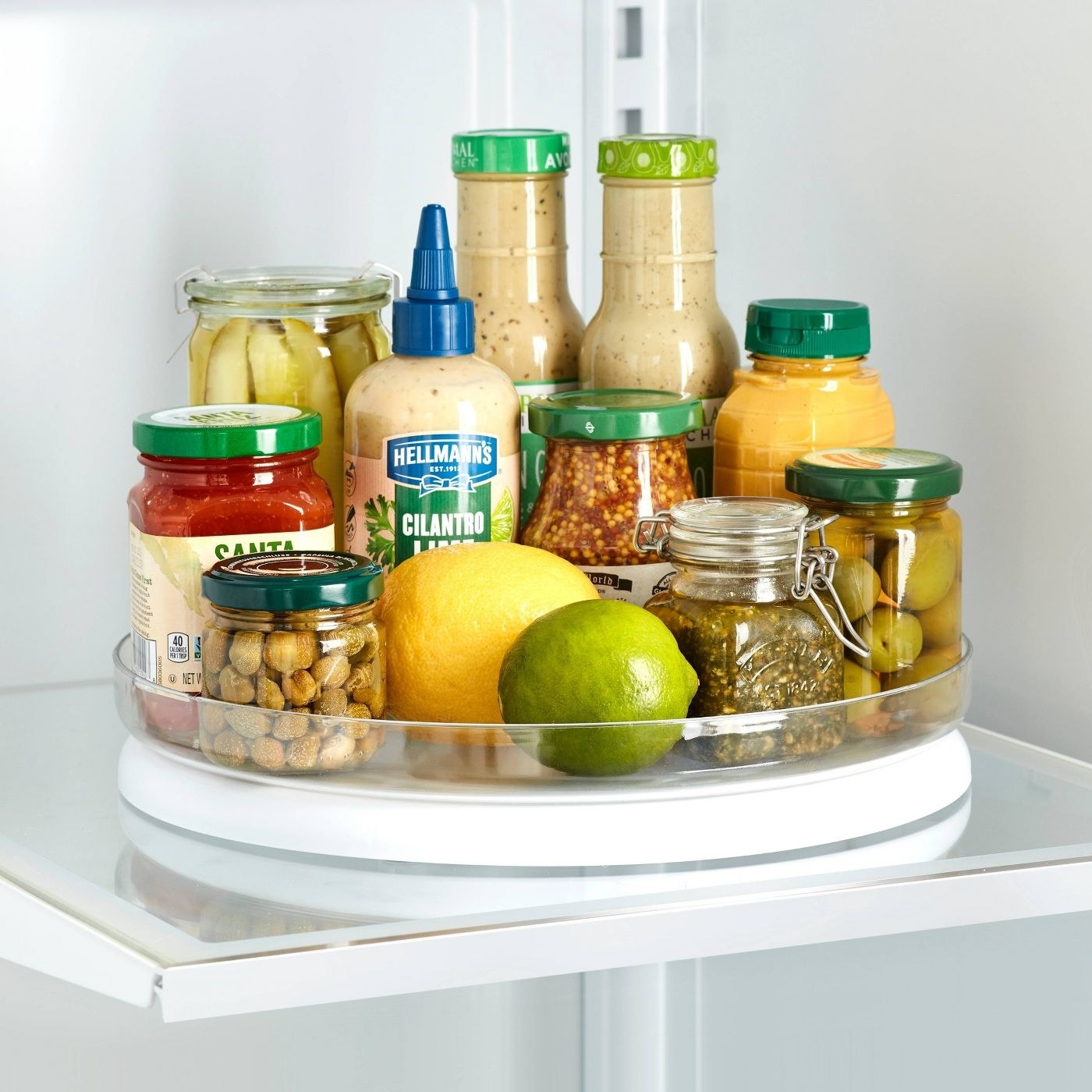 White and clear turntable with jars of olives, fresh lemons, and dressing inside a fridge