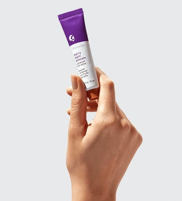 A person holding a tube of the berry balm dot com