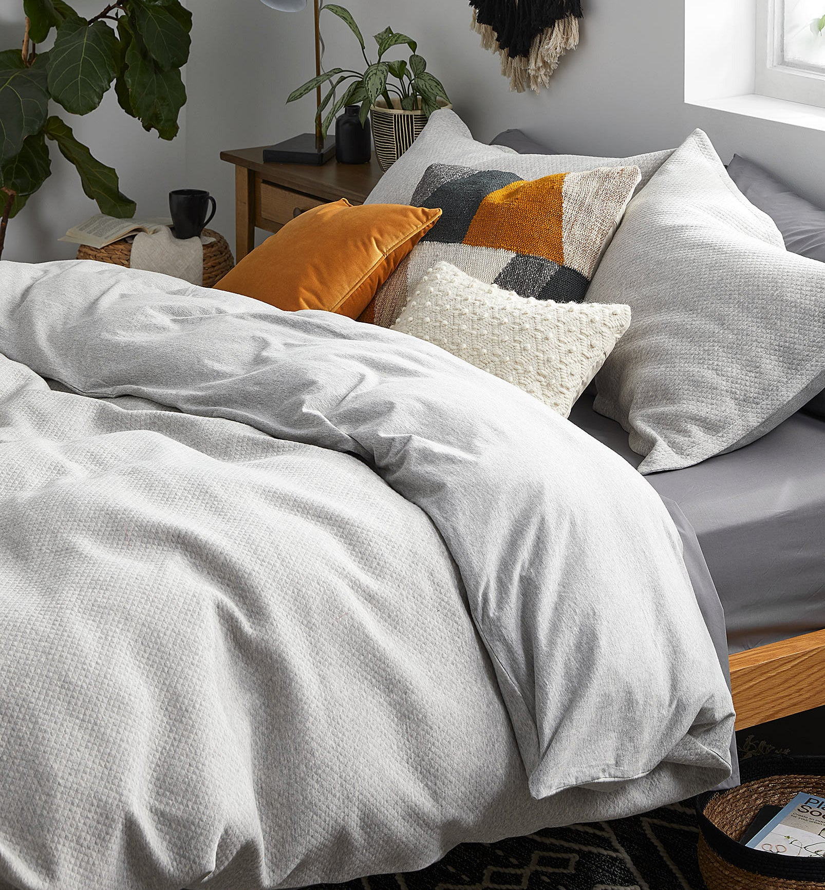 A bed with a thick duvet and pillows on it