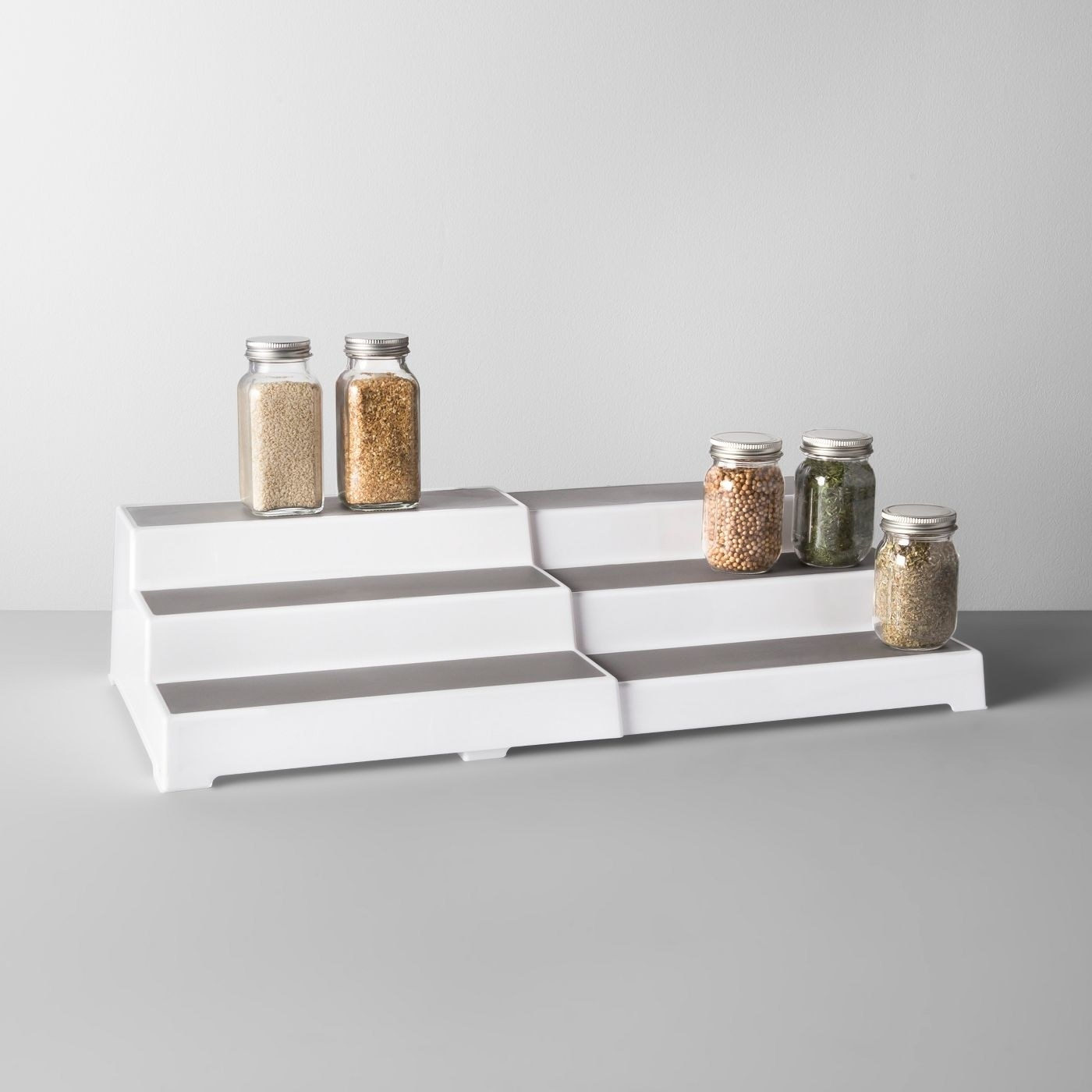White and gray expandable shelf with spice jars on top