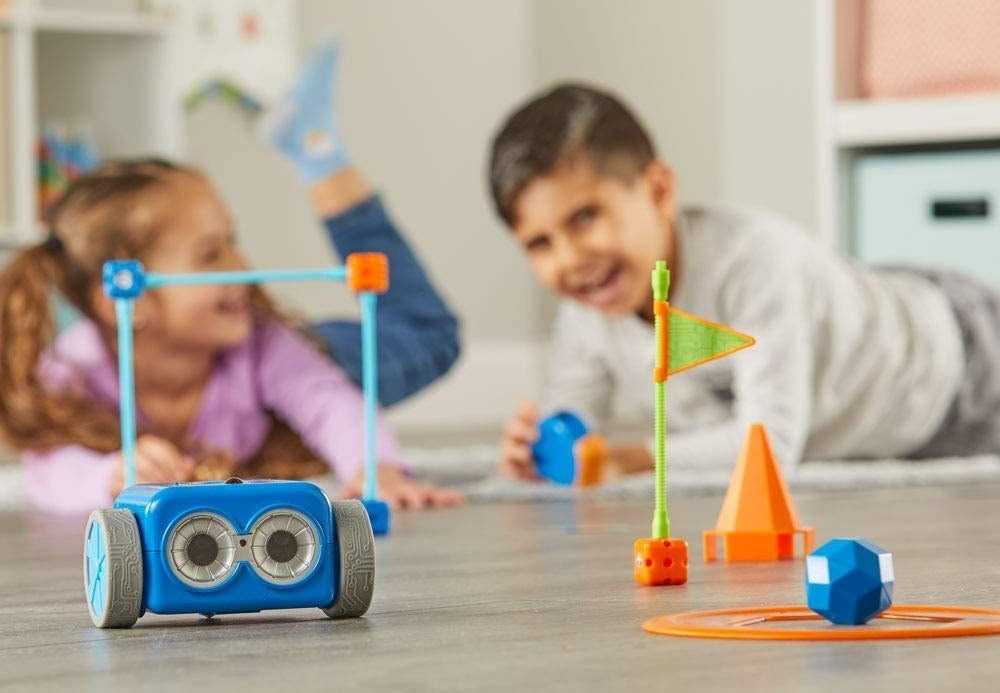 Two child models playing with wheeled blue robot