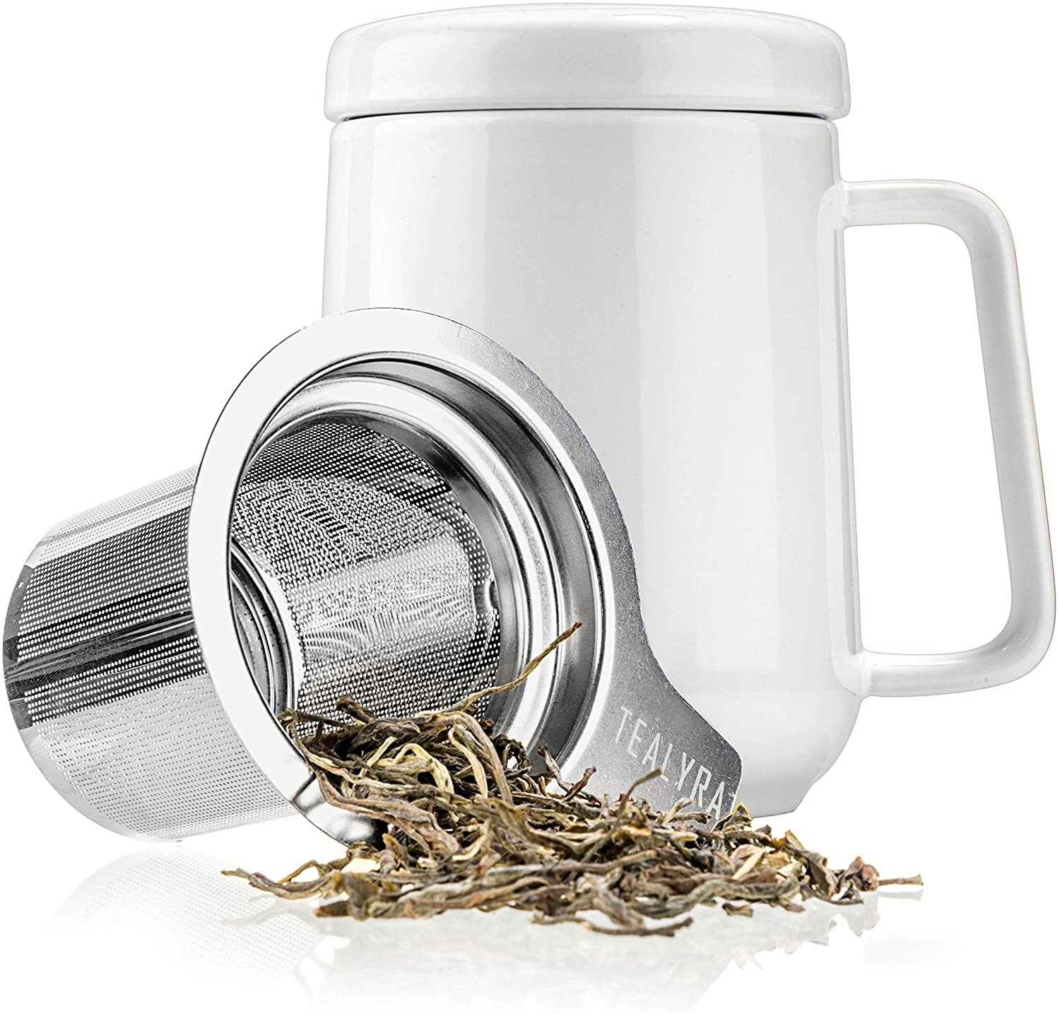 A ceramic mug with a handle and lid A steel tea infuser is sitting in front of with loose tea leaves spilling from it