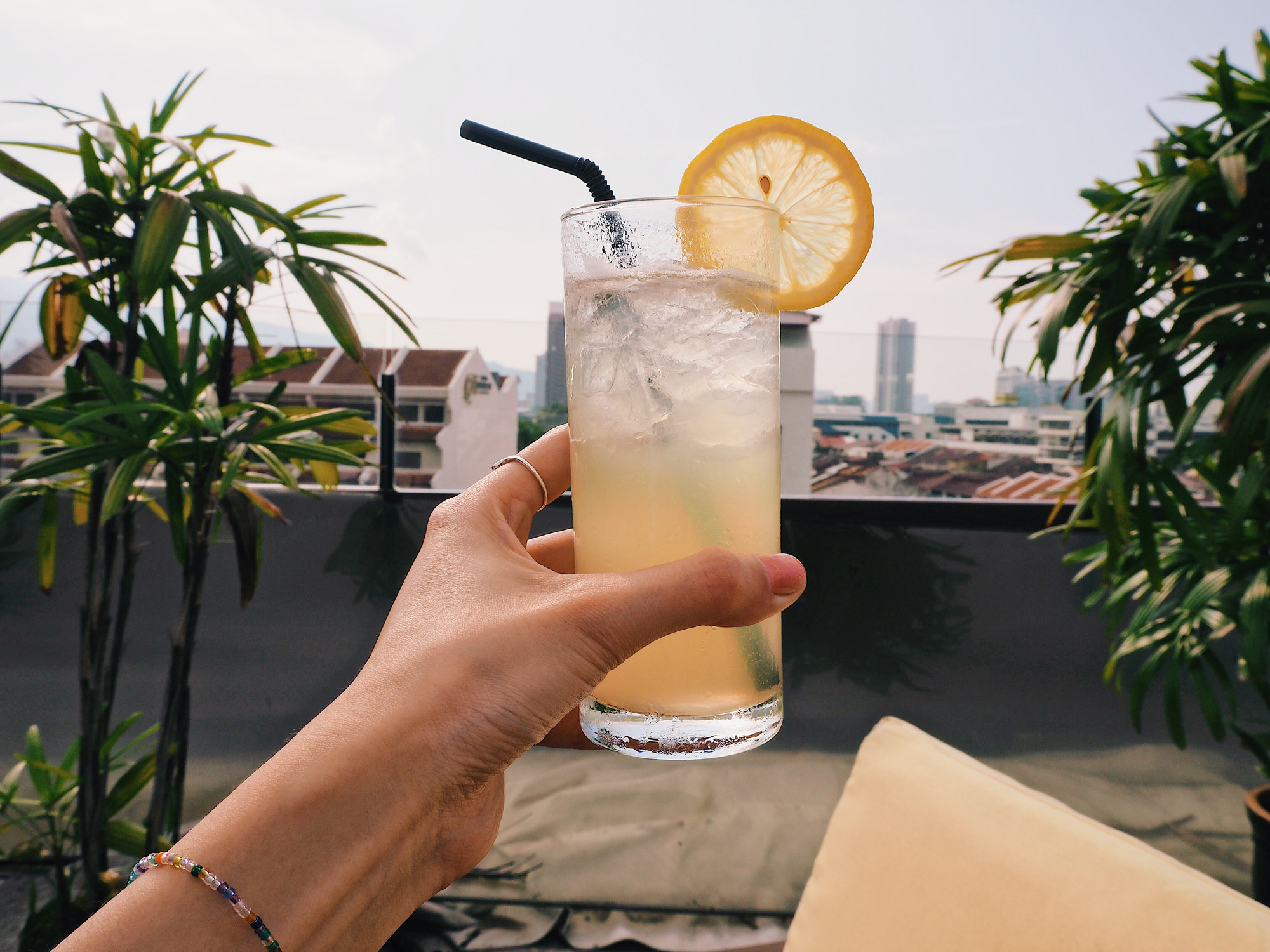A woman's hand holding a cocktail up outside.
