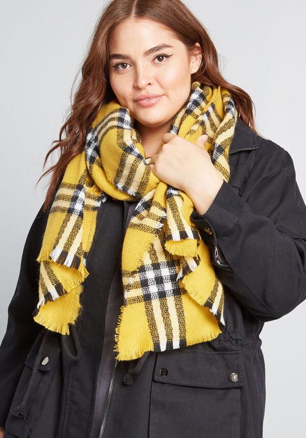 A person wearing a patterned blanket scarf around their neck