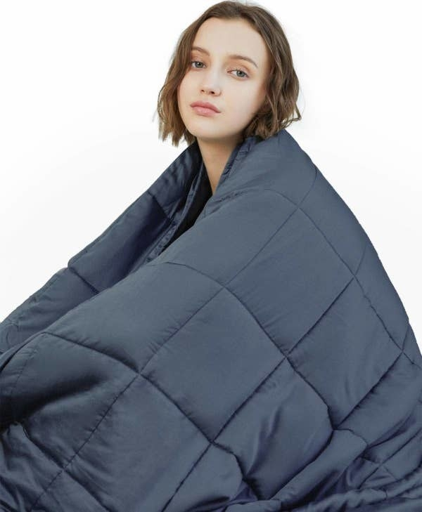 A person with the weighted blanket wrapped around them