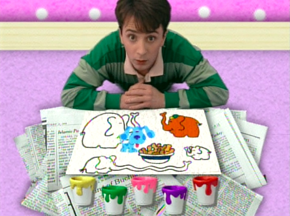 Steve in front of paint buckets and the drawing of elephants Blue is on top of