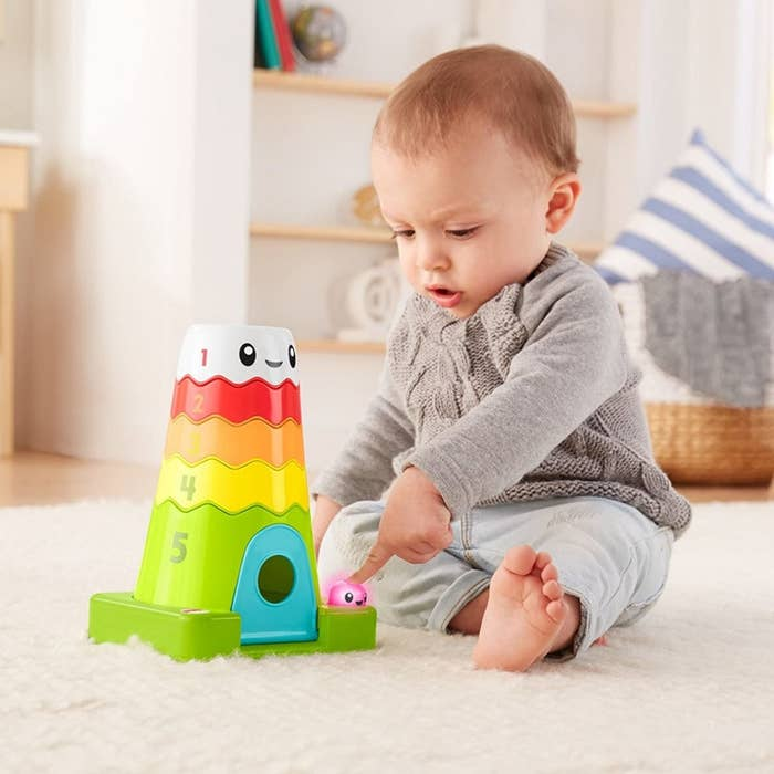 Baby model playing with colorful stackable mountain and plastic bear toy