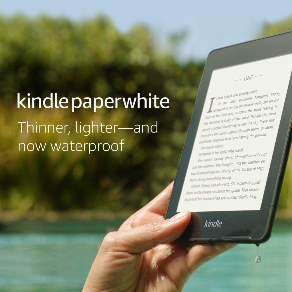 "Hand holding the black Kindle with the text ""thinner, lighter — and now waterproof"""