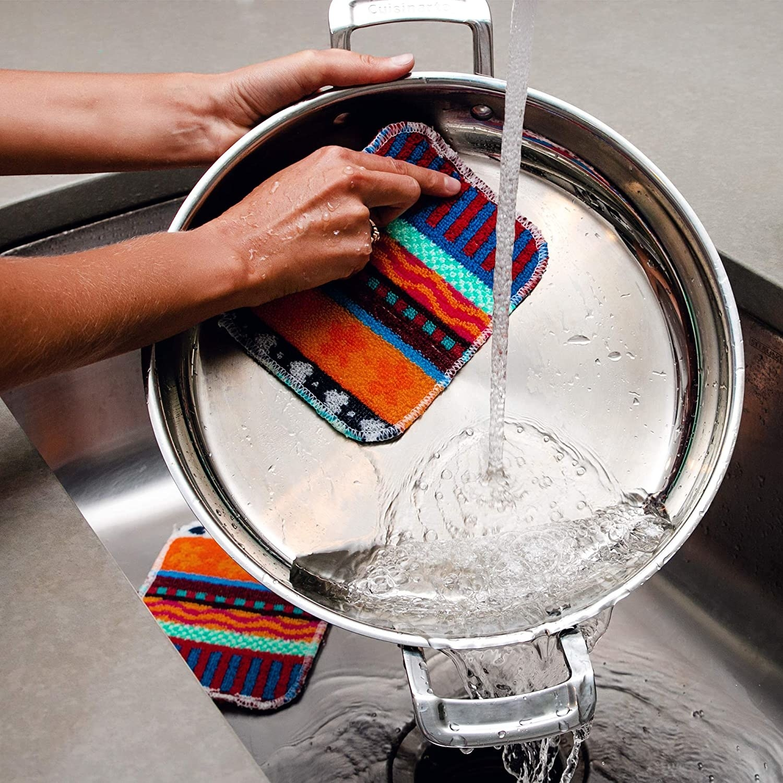 A person scrubbing a pan with a scrubber