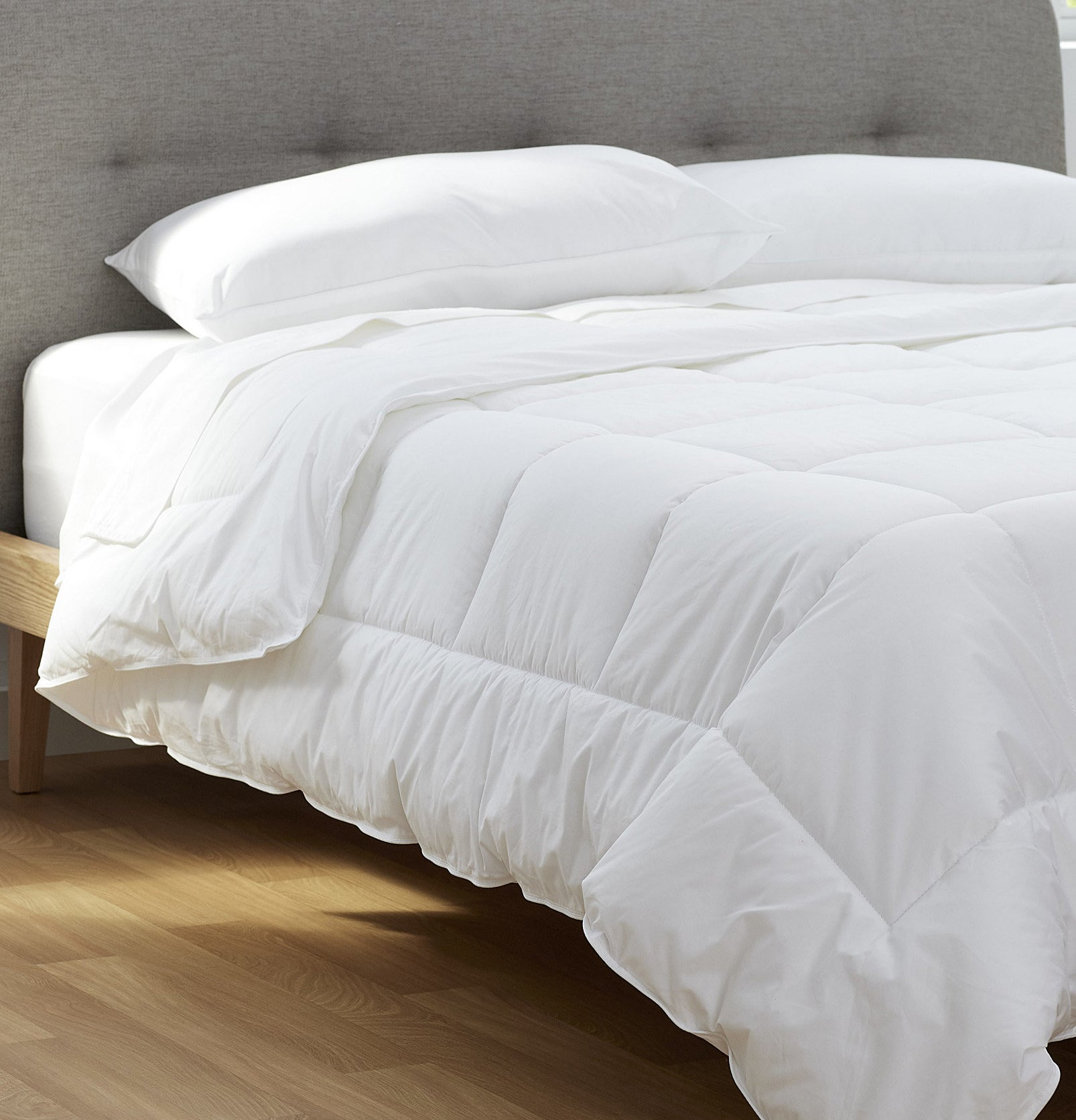 A thick duvet on a bed with two pillows