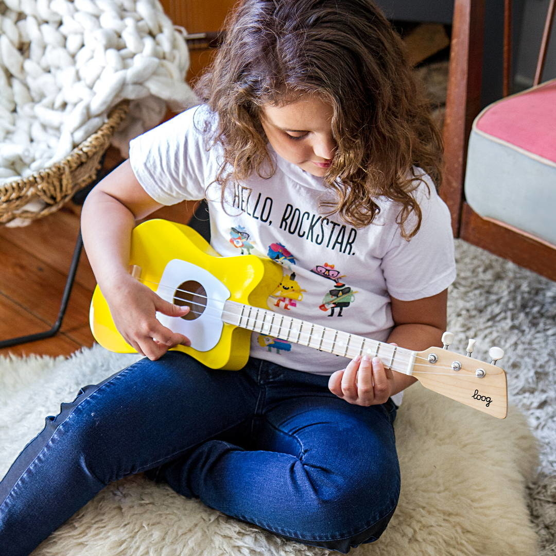 Child model playing a red, three-string guitar with note codes scattered about