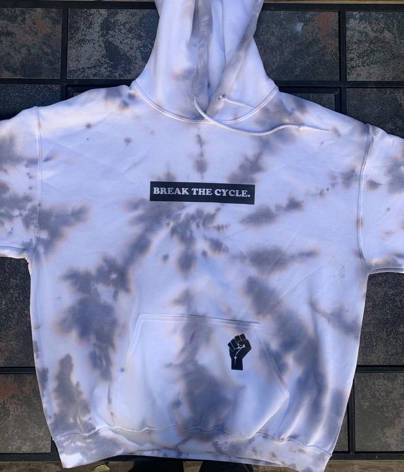 "a white-based tie-dye hoodie featuring the words ""break the cycle"" across the center and BLM fist on the hoodie pocket"