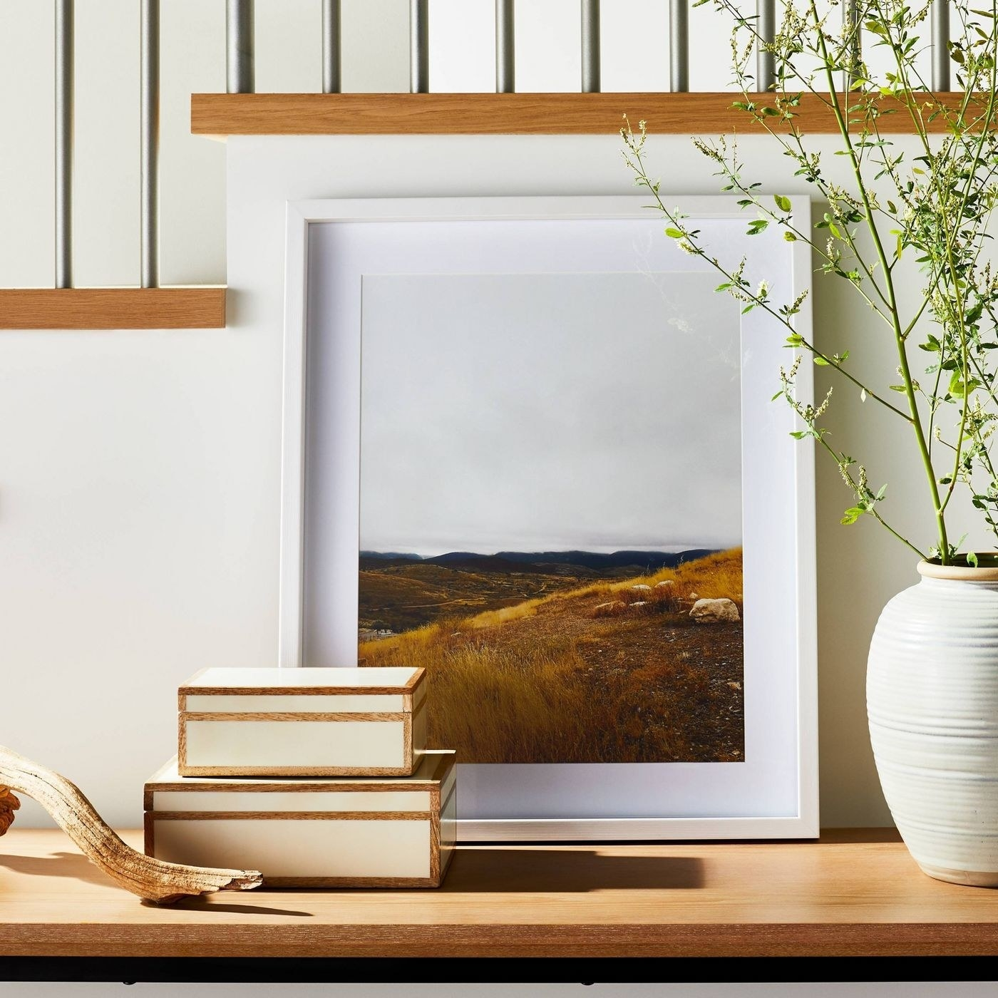 Wood and ivory boxes next to large white picture frame and vase with plant