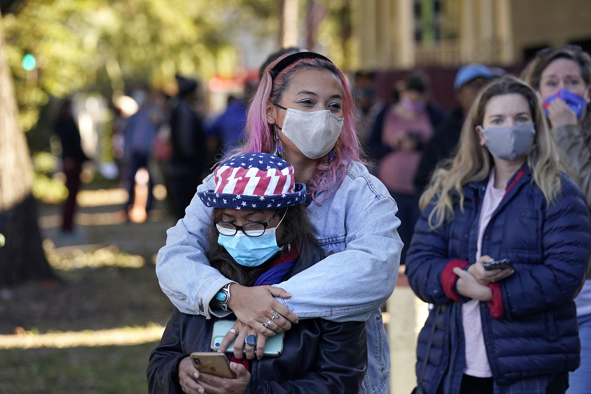 A young woman with pink hair hugs her mother who is wearing a mask and a flag hat