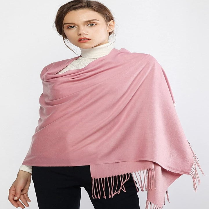 Model wearing scarf draped over her chest as a shawl