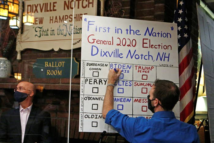 A handwritten vote count is updated by a man in marker