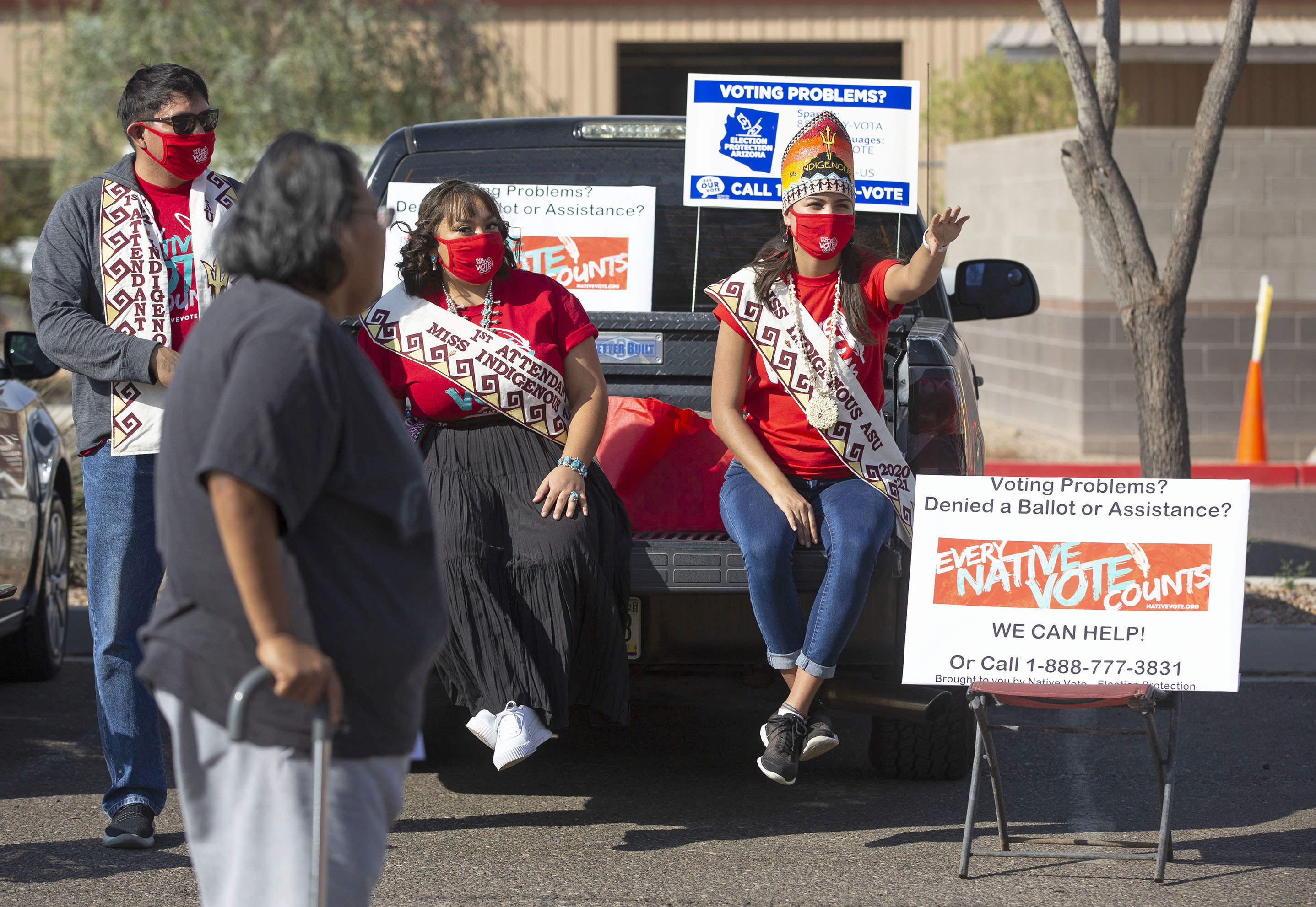 Women wearing banners and face masks sit on a pickup and direct a woman with a cane