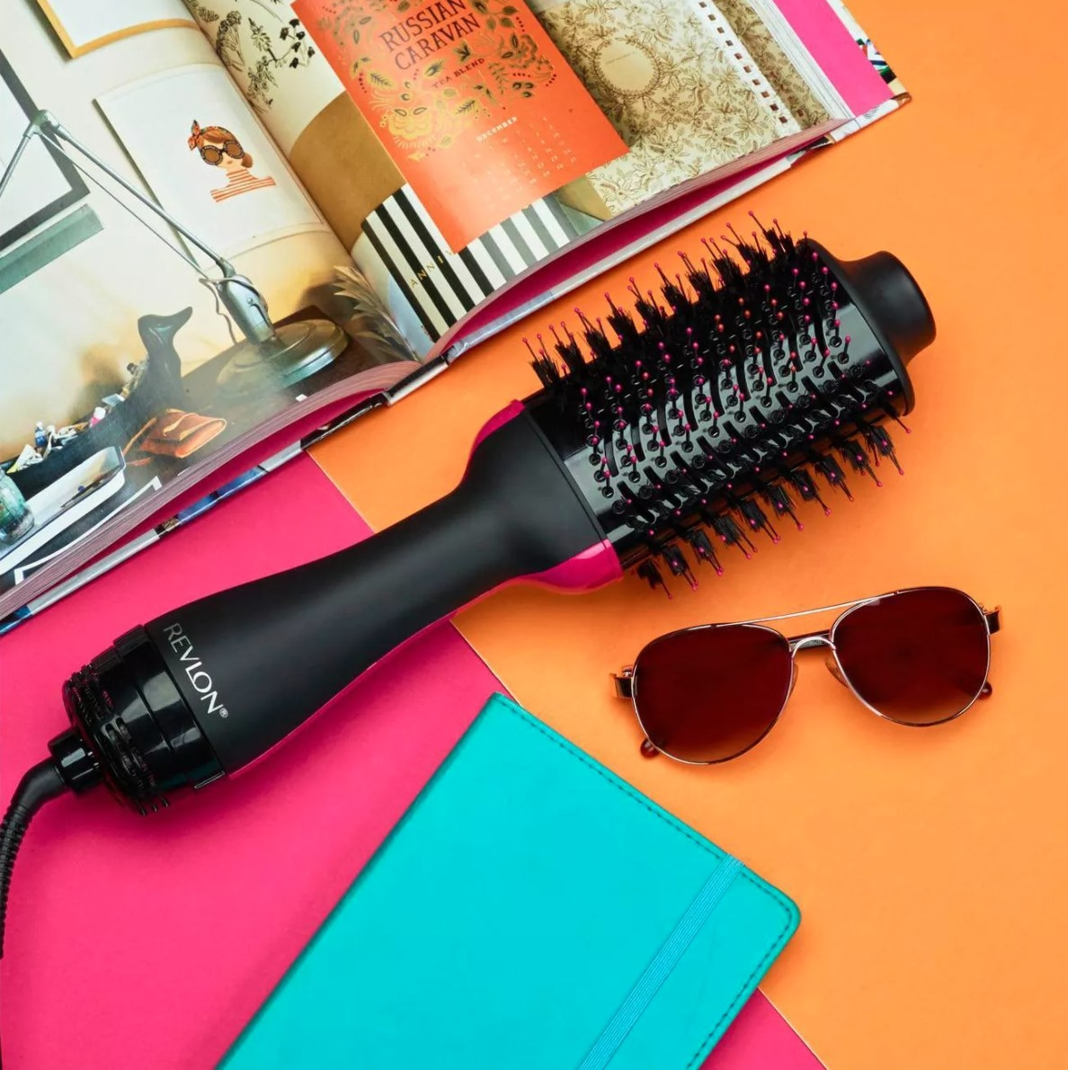 revlon one-step hair dryer and magazine on colorful background flat lay