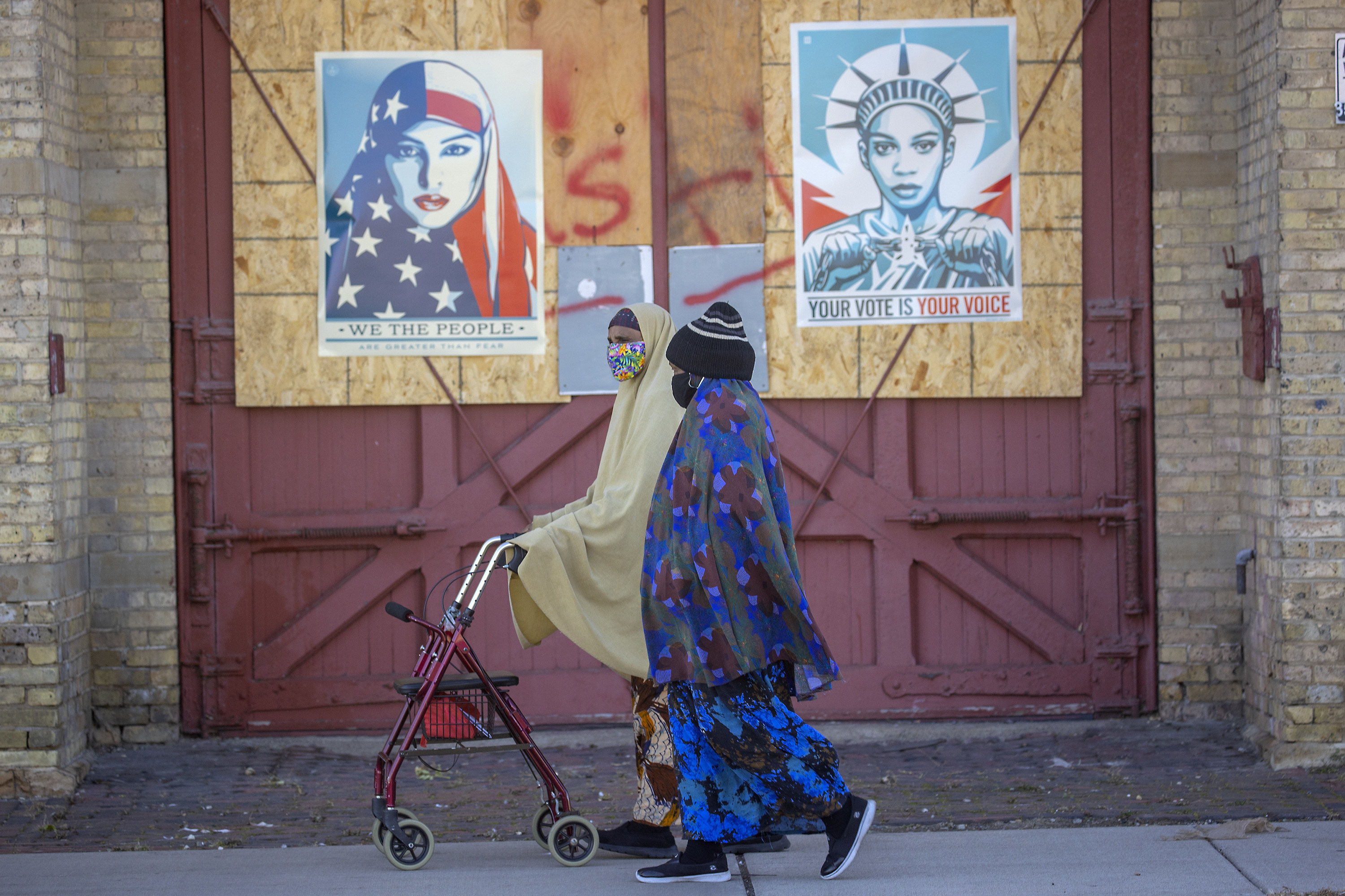 Two women in hijabs walk by signs of we the people