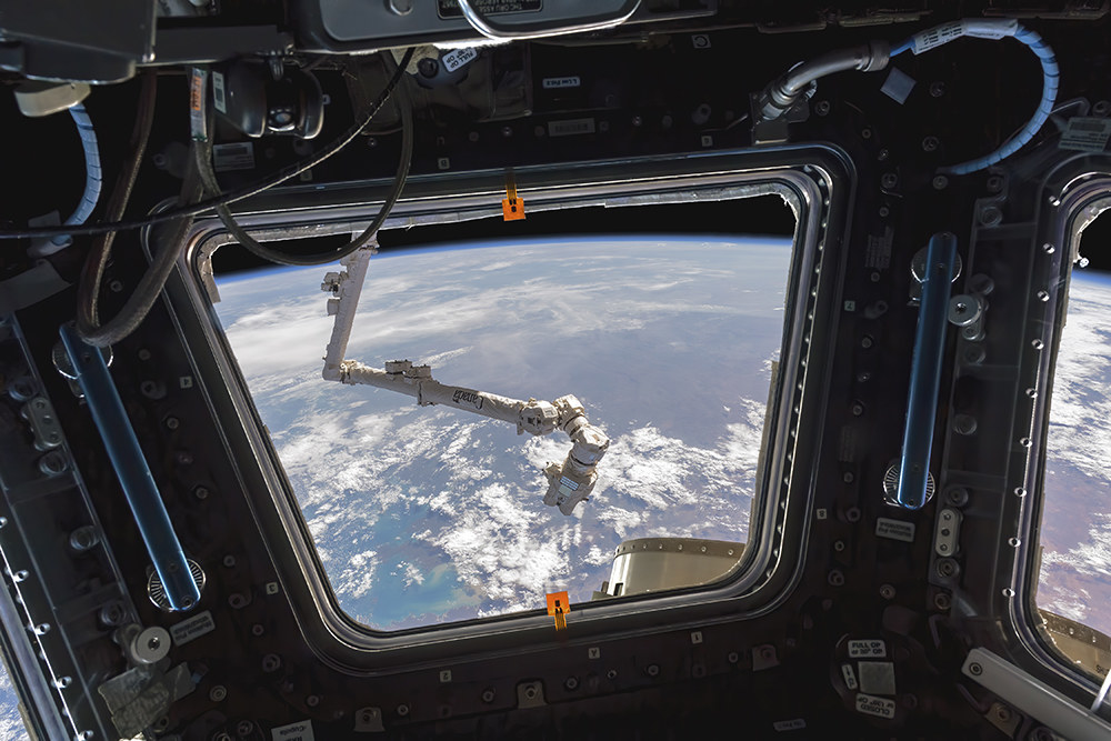 A robotic arm seen outside a window with Earth in the backgroud