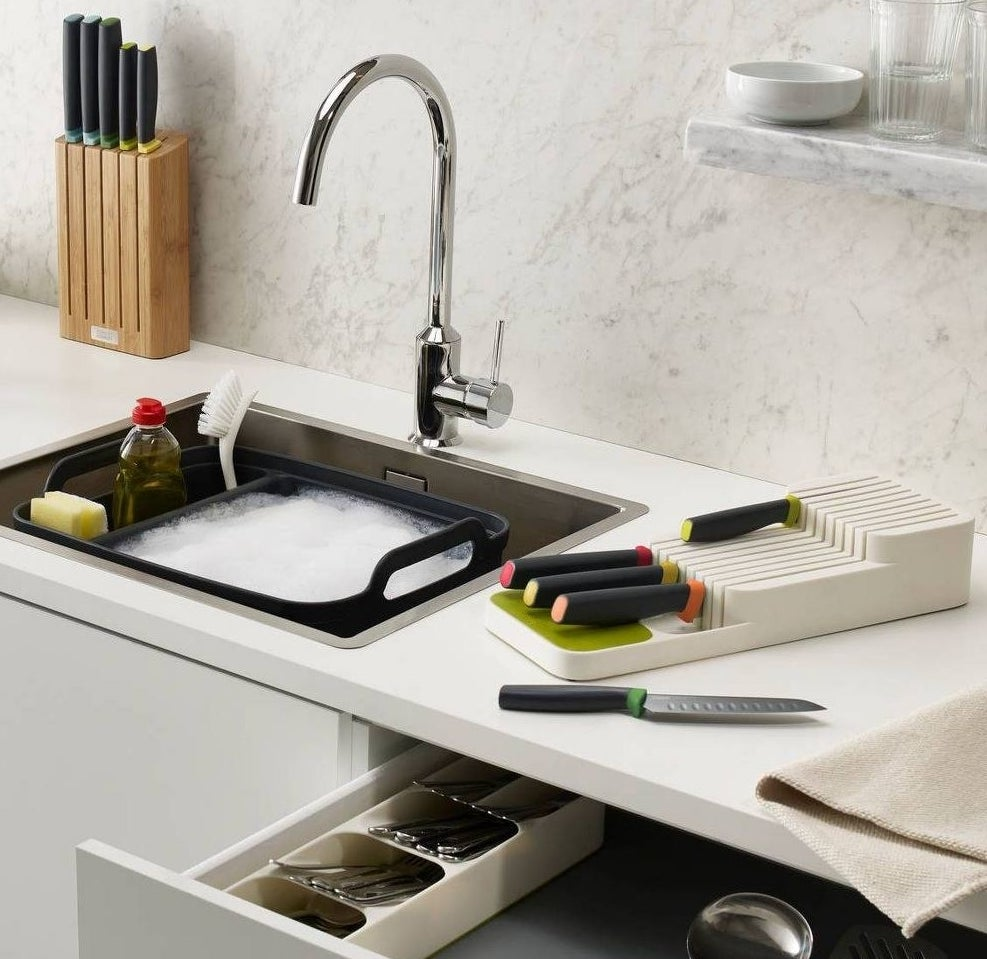 White knife organizer with black knives on a kitchen counter