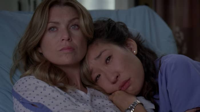 Meredith and Cristina hugging in a hospital bed