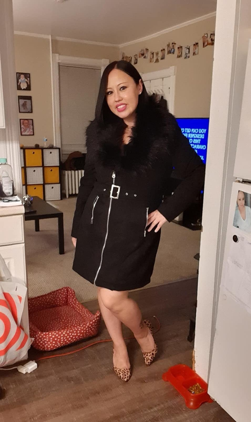 Reviewer wearing the knee-length jacket in black with silver long zipper and belt in the middle